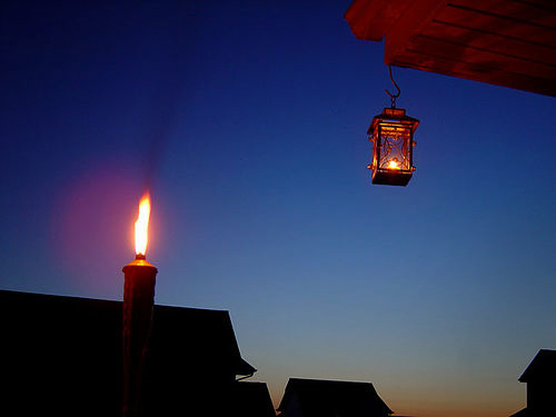 A tiki torch at night with a lantern